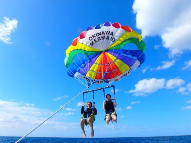 水納島でパラセーリングを楽しむ2人
